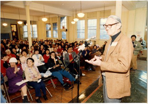 "13 June 2019 Posted. Lung ""Pop"" Chin, master storyteller and Chinatown elder, was beloved by the generations of community youth with whom he worked, especially for organizing sports teams and events. Mr. Chin, shown here having just addressed the room, was key to organizing the 1988 reunion; Museum of Chinese in America (MOCA) Institutional Archives. Lung ""Pop"" Chin,故事大师和唐人街长老,深受年轻人爱戴,特别是他组织的体育队和运动项目。照片中正在讲话的他是MOCA组织1988年第23公立小学聚会的关键人物;美国华人博物馆(MOCA)机构档案"