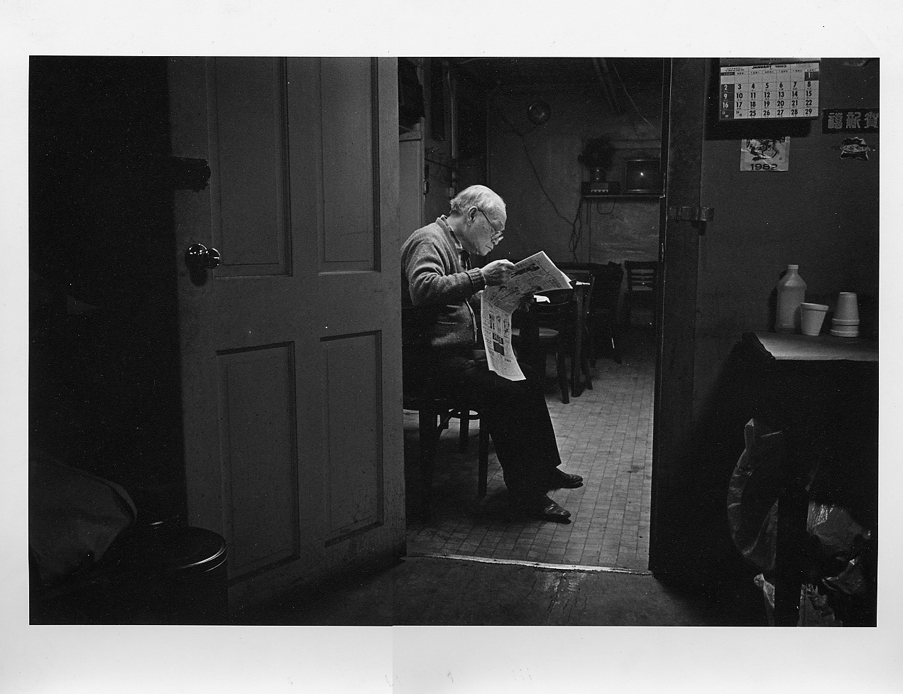 04 June 2019 Posted. An old Man Reading in a Bachelor Apartment located ae 68 Byard Street, Photograph taken by Bud Glick. Museum of Chinese in America (MOCA) Collection. 一位老人在位于摆也街68号的单身公寓读报纸,照片由Bud Glick拍摄,美国华人博物馆(MOCA)馆藏