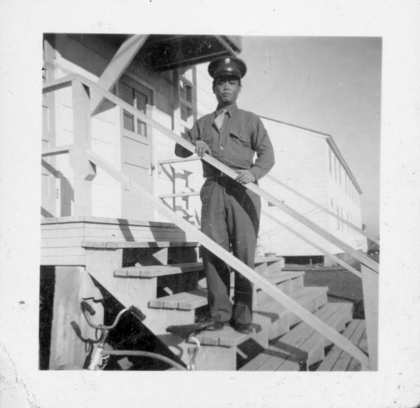 11 April 2019 Posted. Shuck Wing Chin in uniform standing on the steps to a military barracks. Museum of Chinese in America (MOCA) 111 Mott Street Collection. 身穿军装的甄灼荣站在军营的台阶上。美国华人博物馆(MOCA)勿街111号馆藏档案