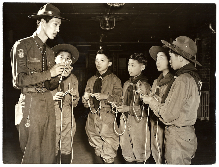22 October 2019 Posted.  Assistant Scoutmaster Horace Eng teaching a group of five scouts how to tie knots, 1942, Courtesy Kenneth & Helen Chan, Museum of Chinese in America (MOCA) Collection. 助理童子军英负责人Horace Eng正在教五位童子军成员如何系绳结,1942年,Kenneth & Helen Chan捐赠,美国华人博物馆(MOCA)馆藏