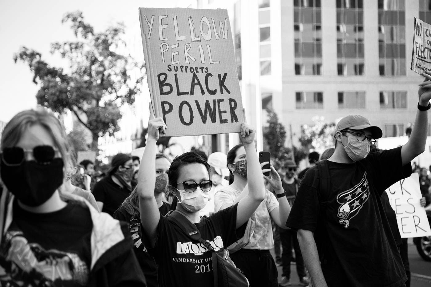 """Asians for Black Lives: An unnamed woman at a Black Lives Matter rally near the White House, Washington DC. She is holding a sign that says """"Yellow Peril Supports Black Power.""""  Photograph by Mengyu Dong"""